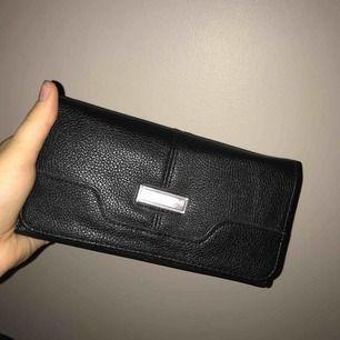 En svart plånbok med bra plats för telefon och kort osv. Rymlig. En silver detalj på framsidan.