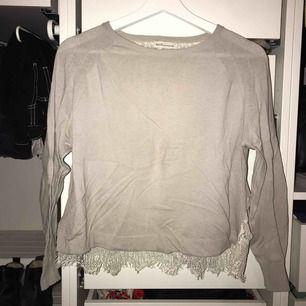 Ljusgrå tunn stickad tröja med spets detaljer vid nedre kanten. Passar storlek S
