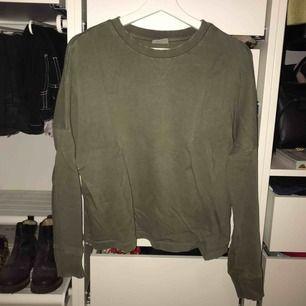 """Grön tjocktröja/ långärmad tröja från Weekday i """"tvättat"""" material alltså att den är inte helt jämn i färgen."""
