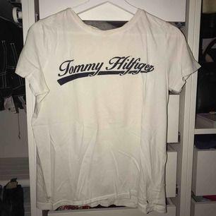 """Vit t-shirt med tryck """"Tommy hilfiger"""" på framsidan i mörkblå färg."""