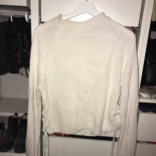 Vit stickad tröja från crocker med snörning vid sidan på båda sidor av tröjan.