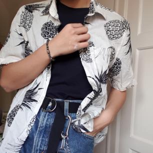 En svartvit hawaii-skjorta från H&M med Ananas motiv.