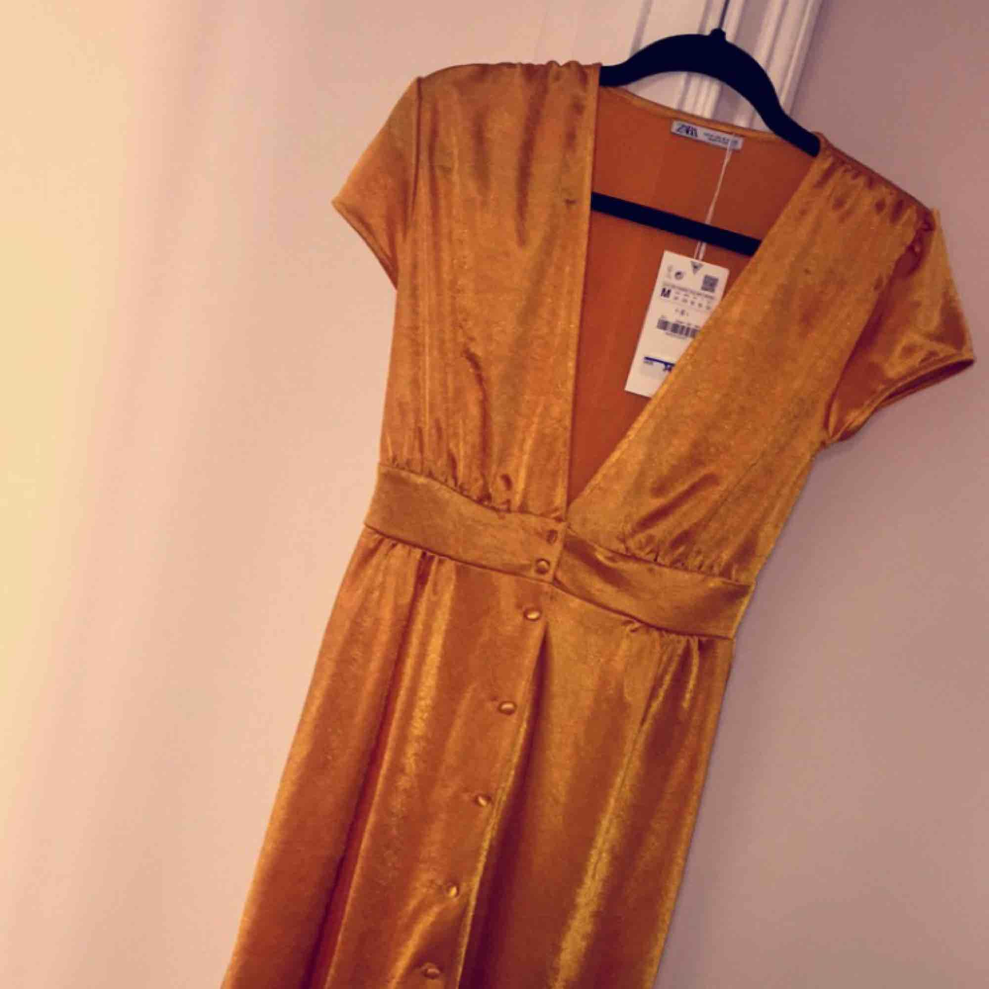 Oanvänd gul/guldig klänning från zara med prislapp kvar. Fin v-ringning och knappar längst hela framsidan. Mjukt och fint material som får klänningen att glänsa fint. Säljer den då den inte är rätt storlek för mig. . Klänningar.