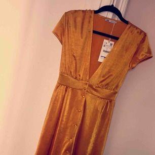 Oanvänd gul/guldig klänning från zara med prislapp kvar. Fin v-ringning och knappar längst hela framsidan. Mjukt och fint material som får klänningen att glänsa fint. Säljer den då den inte är rätt storlek för mig.