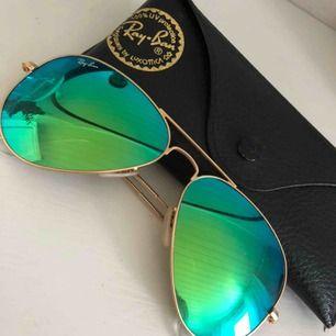 Solglasögon från RayBan. Grönt spegelglas och gullig båge. Original glasögonfack medföljer. Köparen står för eventuell frakt.