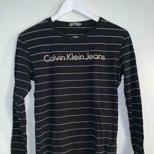 En svart tröja med vita ränder från Calvin Klein Jeans i nyskick! Storlek (S) i dammodell men passar mig som är en S/M  Nypris: 500kr Mitt pris: 200kr  Obs! Priset är diskutabelt och tröjan kan hämtas runt Halmstad eller Gislaved området.