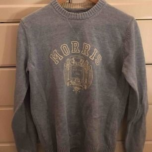 En ljusblå, stickad Morris tröja i mycket bra skick. Inga tydliga slitningar. Herrstorlek S.  Möts upp i Stockholm.