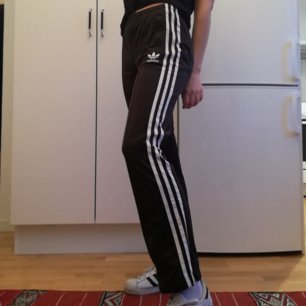 Klassiska svarta Adidas trackpants med vita stripes i stl 36. Fickor i sidorna och dragkedja längst ner på benen. I jättebra skick förutom ett litet minihål på ena benet, syns på bild 2. Frakt 59 kr.