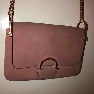Smuts rosa axelremsväska från H&M i bra skick förutom märken på baksidan av väskan. Köpt för cirka 200kr för ungefär ett år sen, ganska använd. 70kr inkl frakt!