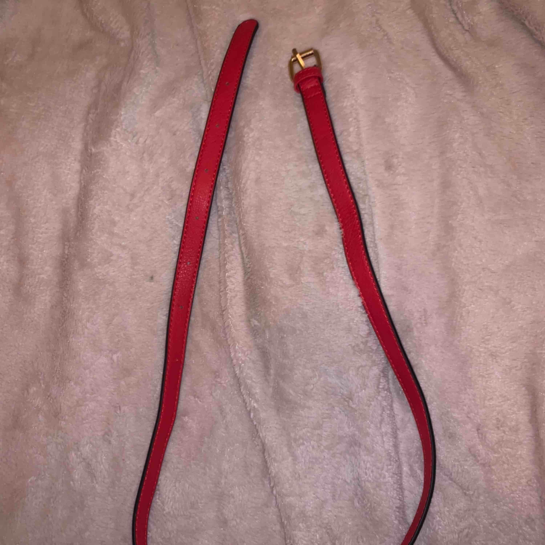 Rött skärp med svarta sidor. Aldrig använt Passar S/M. Accessoarer.