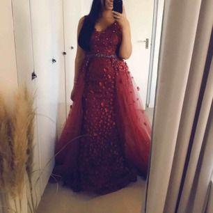 Säljer min vackra festklänning/aftonklänning  Köpt från Södertälje men minns inte butiken  Klänningen är i färgen vinröd med en kjol som är avtagbar. Klänningen har blommor i samma färg och dekorerad med stenar.