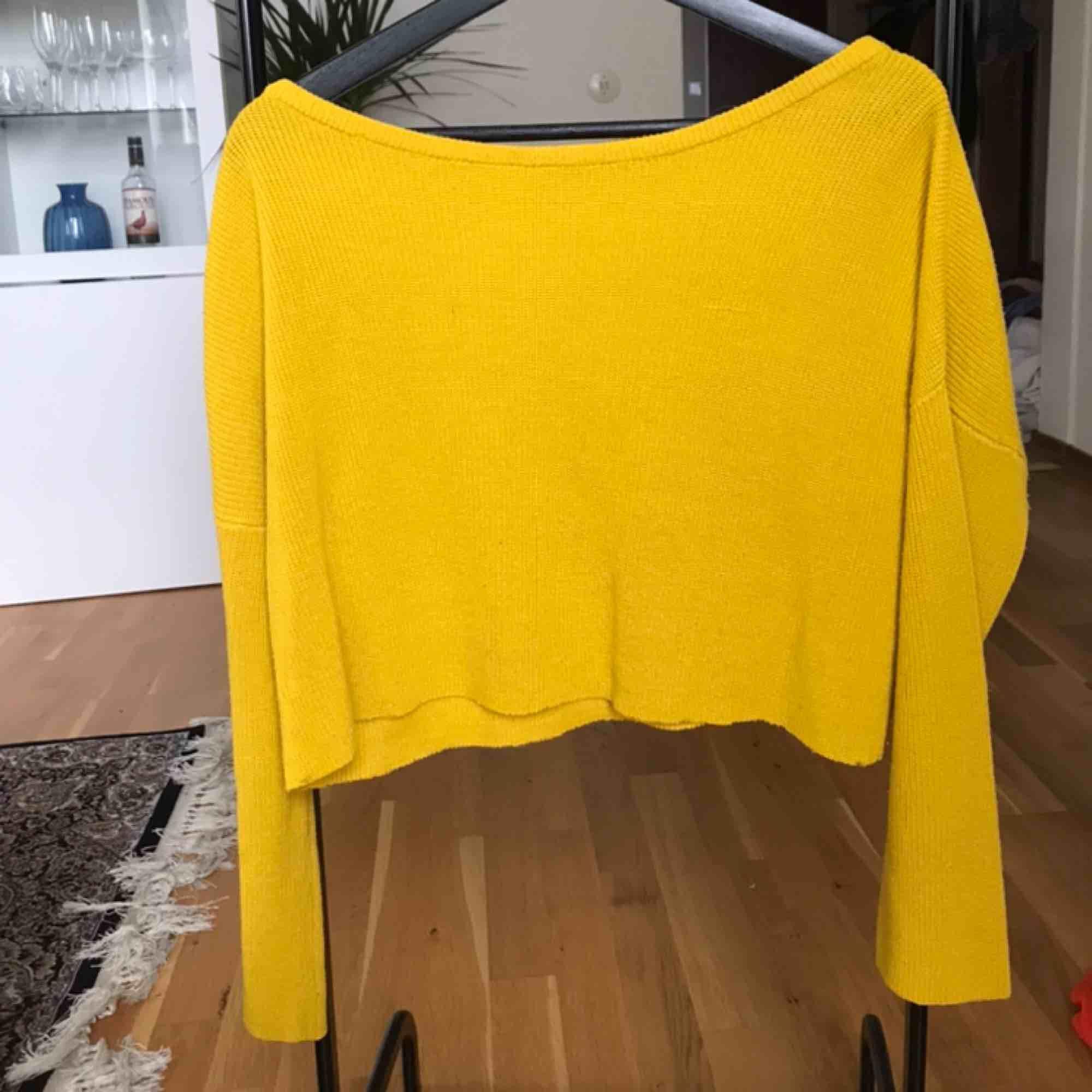 Stickad gul tröja, avklippt på längden. Stickat.