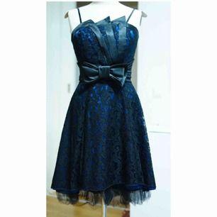 Knälång klänning i svart & marinblått. Spetsdetaljer & ett bälte med rosett. Reglerbara axelband. Storlek 34-36. Väldigt bra skick.