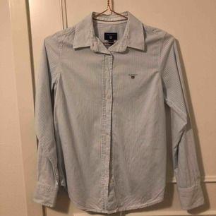 ljusblå och vitrandig gant skjorta i strl 34! inte använd alls många gånger och därav bra skick. kommer inte till användning då den dels är för liten och inte min stil längre :/