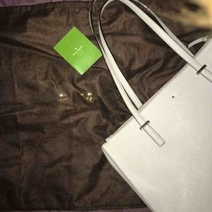 Ljus grå/naturfärgad Kate Spade väska i bra skick. Köpt i New York. Original pris: 4000kr. Dustbag och care card medföljer.