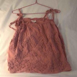 Fint rosa linne med brodyr. Axelband som man knyter själv och kan reglera storleken. Knappt använd. (Storleken passar från XS-M sitter lika snyggt på dessa storlekar) kan mötas upp eller frakta!