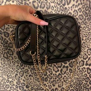 Svart väska med guld kedja från H&M, väskan är aldrig använd och ser helt ny ut.