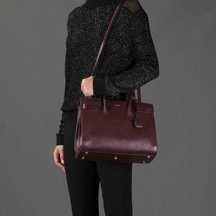 Tidlös läderhandväska i burgandy färg! Notera repa på framsidan! Lås, nycklar, axelrem och dustbag ingår! Fick den som gåva så jag har inte kvitto så kan inte garantera äkthet!  Bredd ca. 31cm Höjd ca. 21,5cm