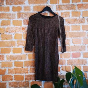 Super fin guldglittig klänning från Monki. Tight, trekvartsärm och storlek XS. I fint skick, på enstaka ställen har tråden i guldet