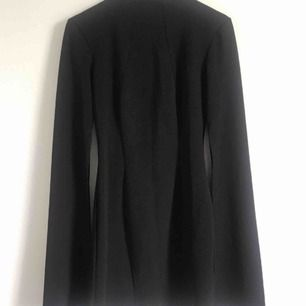 Svart kort klänning från märket Zack London. Köpt från Bubbleroom. Storlek UK 10 - 36  Öppen rygg och slits i armarna.  Använd 1 gång
