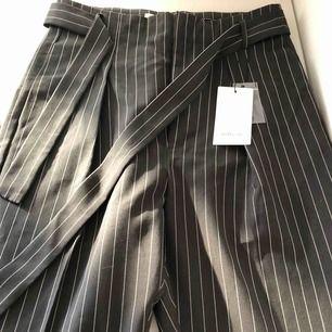 Svarta/grå kostymbyxor med vita ränder och bälte i midjan. Helt nya med prislapp kvar. Originalpris 1200