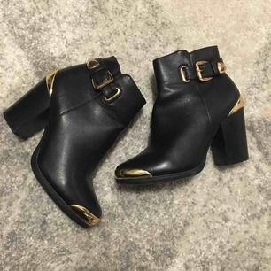 Snygga svarta, höga boots med guld detaljer, bra skick, knappt använda. Säljer pga för små. Köparen står för frakt, betalning via swish