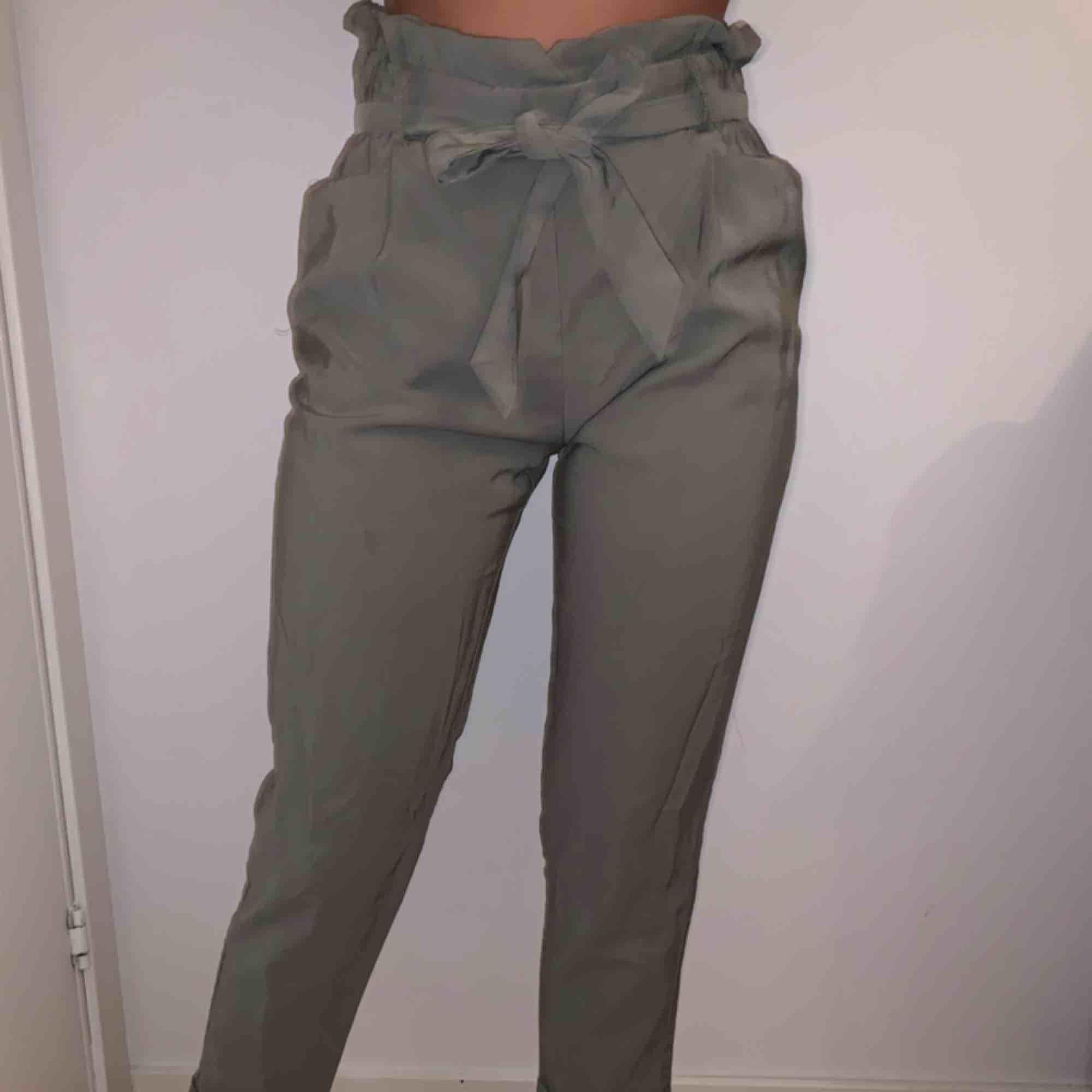 Gröna byxor i paperbag-modell . Jeans & Byxor.