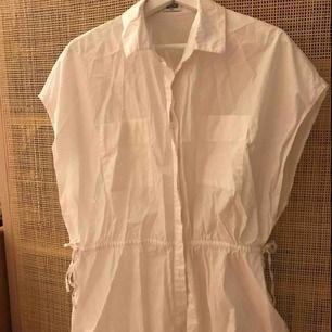 Skjorta i oversizemodell, men markerad i midjan. Köparen betalar eventuell frakt.