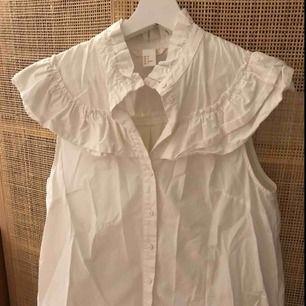 Kortärmad skjorta med detaljer i krås. Köparen betalar eventuell frakt.