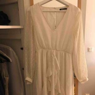 Jättefin vit klänning med volanger. Ärmarna är även mesh med prickar (se bild 2). Det är dessutom vringning som är jättefin. Säljes på grund av att den är för liten.