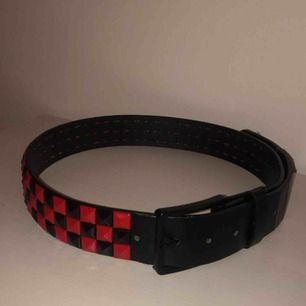 Fint bälte med röda och svarta nitar. Lite slitet i kanterna men inget som syns när det sitter på. Alla nitar sitter på.
