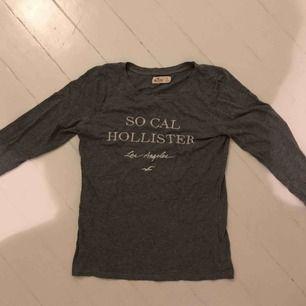 Grå tröja med text från Hollister, strl S.