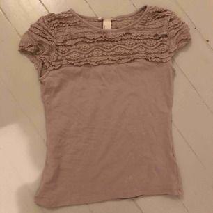 Jättesöt T-shirt med spets i en beige färg, strl S.