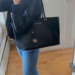 Säljer äkta Michael Kors väska. Använd ett antal gånger därav ganska slitna väskband, men inga större skador. Säljer väskan pga att det inte passar min stil längre. Bredd 48 cm. Höjd 29 cm. Djup 16 cm.