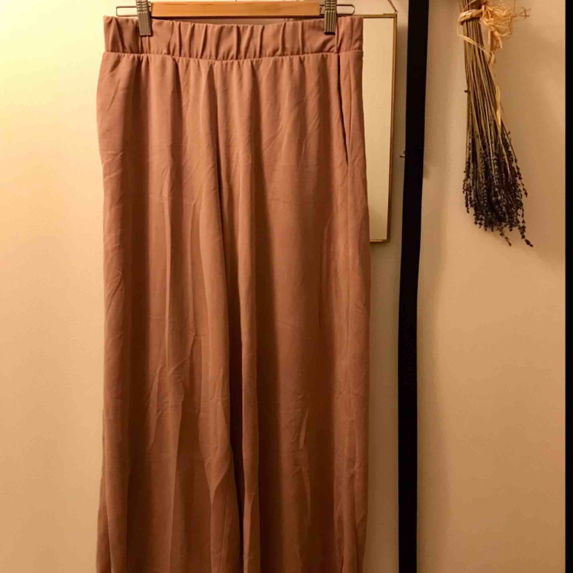 Raka, vida byxor med fickor. Ankellånga, gammelrosa. köparen står för eventuell frakt.. Jeans & Byxor.