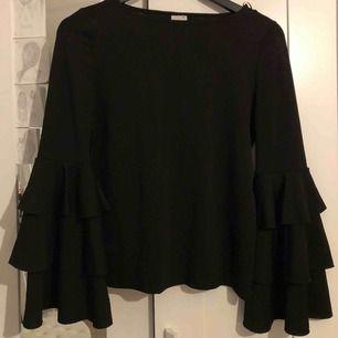 Snygg svart tröja med volanger