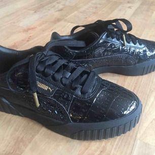 Gratis spårbart frakt Nya Puma Cali Croc sneakers läder svart reptile mönster stl 38 med låda. Säljer pga har för många sneakers. Kan skicka mera bilder.