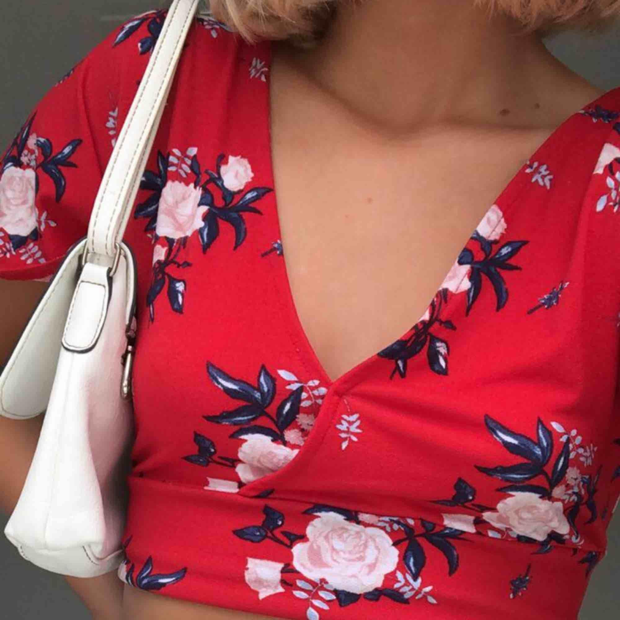 Röd top med blommor i stl M🌹🌹 Kan mötas upp i Linköping eller frakta (köparen står för frakten), använt en gång!. Toppar.