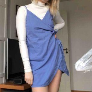 Himmelsblå klänning från Weekday. Helt oanvänd, nypris 450 kr, se prislapp på tredje bilden. Man knyter den via band så därför är den väldigt anpassningsbar, passar nog xs-m. Frakt 30 kr.