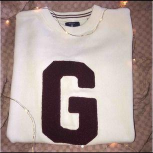 En vit stickad tröja med vinrött G på från gant/kidsbrandstore.  Frakten ingår. Betalning sker via swish. Priset går att diskutera. Nypris 800kr