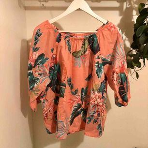Rosa blus med tropiskt print av blad och papegojor samt blommor! Frakt ingår