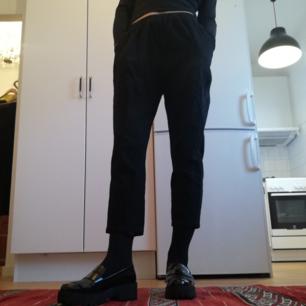 Svarta croppade byxor med resår i midjan, dolda fickor i sidorna och en ficka bak. Köpta secondhand så vet inte vilket material det är men påminner om linne. I begagnat skick. Eftersom det är resår i midjan går det att ha både hög midja och normal/låg. Jag på bilden är 169 cm. Frakt 42 kr.