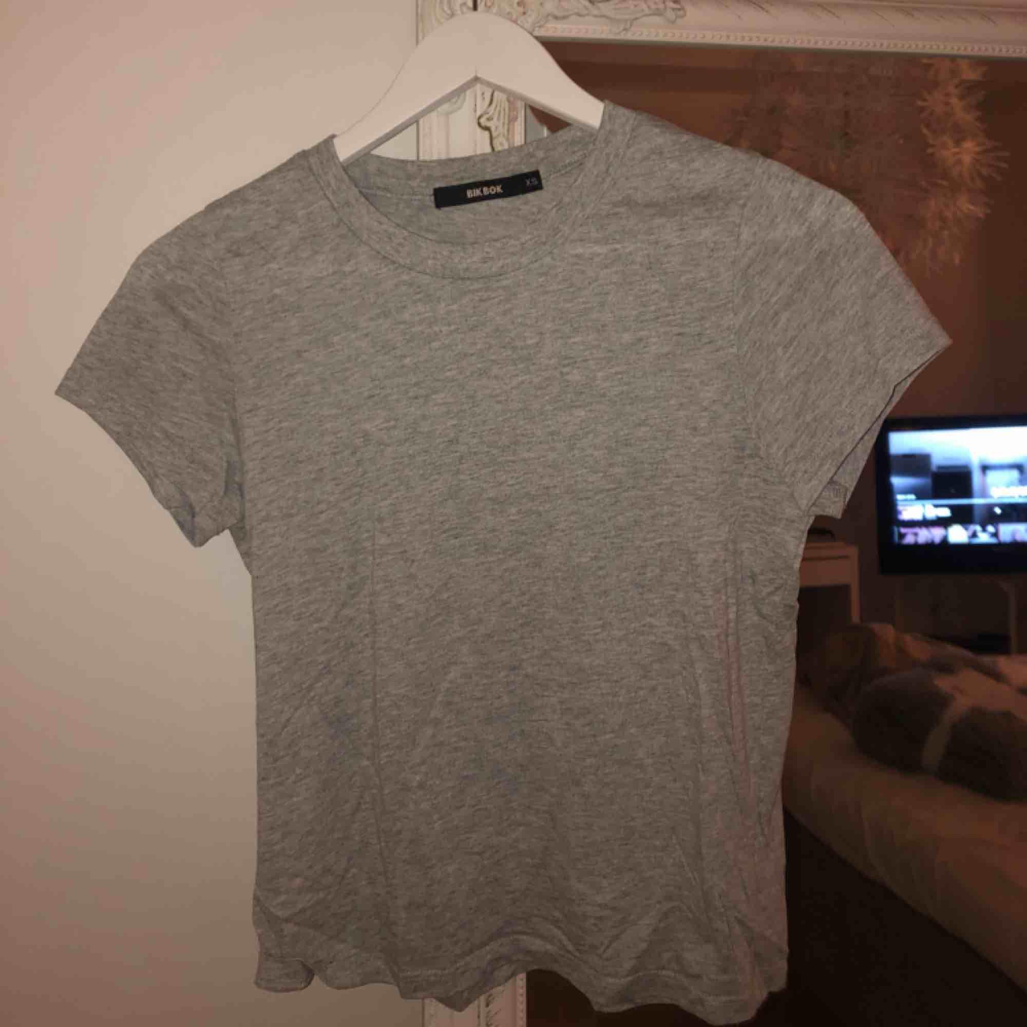 Grå t-shirt med liiiten polokrage från BikBok. T-shirts.