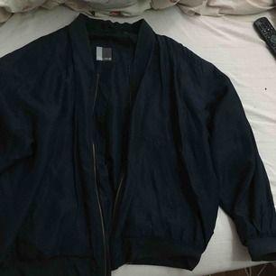 Marinblå välanvänd silkes bomberjacka från humana! slitage på flera ställen (se bilder) men går att laga om man vill. Den är jättetunn och silkig så passar de flesta storlekar men skulle säga M