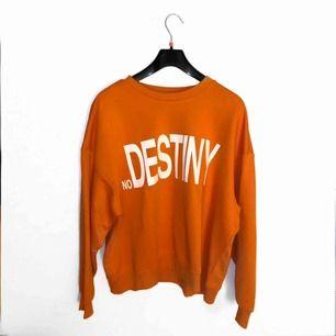 Oanvänd orange sweatshirt från Weekday med texten 'No Destiny' 🦀. Prislappen sitter kvar med nypriset 400kr. Jag står för frakten!