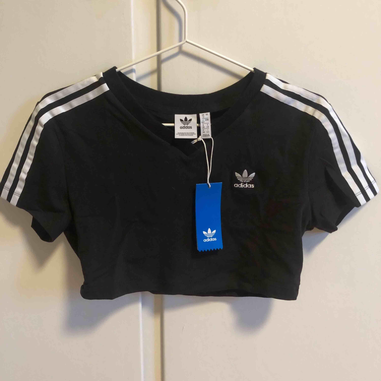 Adidas originals cropped T-shirt i svart. Oanvänd med lappar kvar . T-shirts.