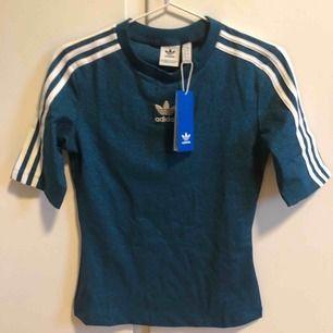 Blå glittrig adidas originals T-shirt i elastiskt men lite hårdare material. Jättefin på!
