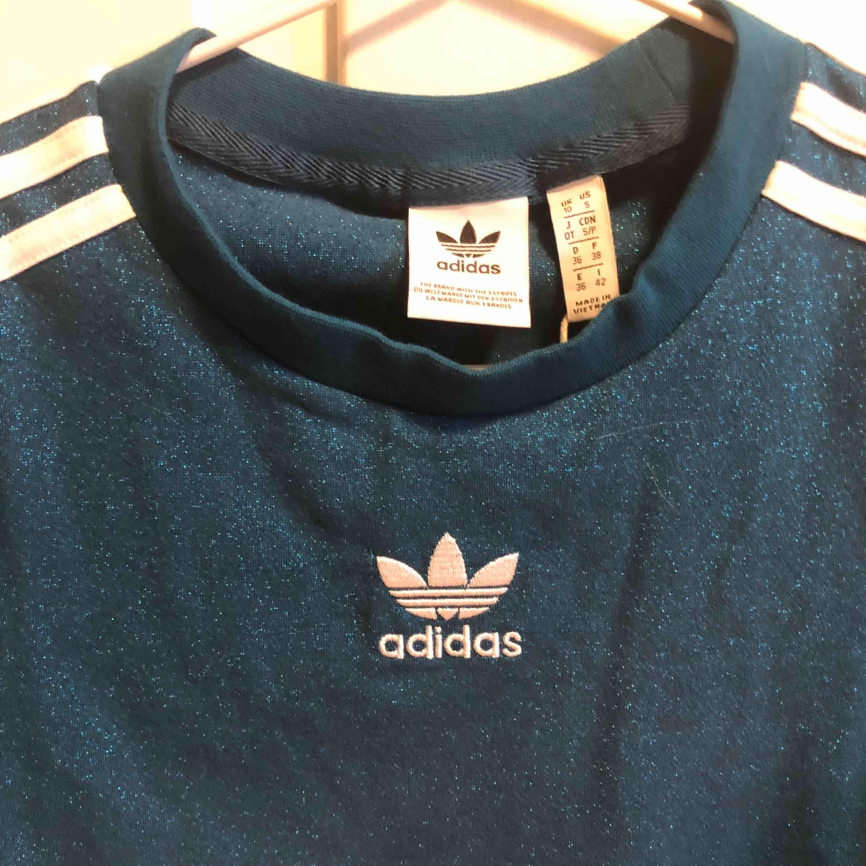 Blå glittrig adidas originals T-shirt i elastiskt men lite hårdare material. Jättefin på! . T-shirts.