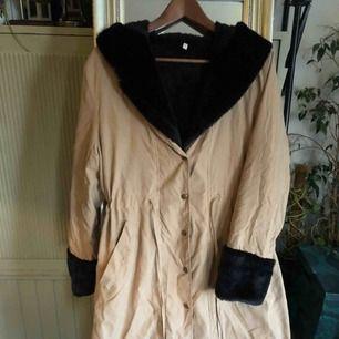 Lång beige jacka med fluffigt svart fejk päls inne och med luva, strl L, 100kr