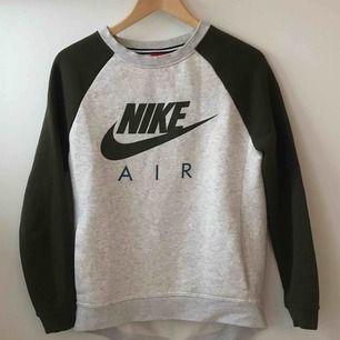 En grå Nike sweatshirt med militärgröna och mörkblå detaljer. Stor i storleken. Fint skick! Köparen står för frakt!